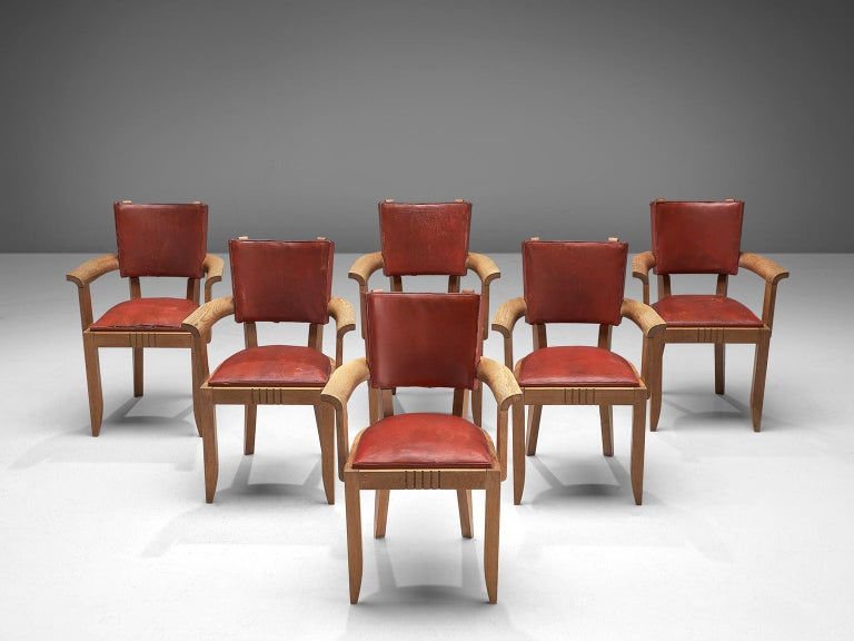 Charles Dudouyt, set of 6 armchairs, leather and oak, France, 1930s  This set of six Art Deco dining chairs is upholstered with deep red leather that has patinated over time. The frame is made of solid oak and features tapered, carved legs. The