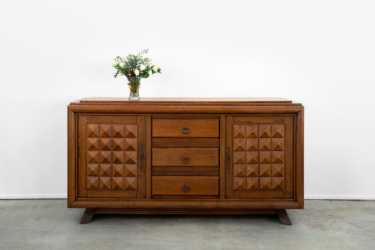 Large scale 1930s French oak cabinet designed by Charles Dudouyt.  Intricately carved detail with plenty of storage - 2 separate cupboards doors that open with shelving inside.  3 drawers in center panel  Recessed angled legs  Gorgeous patina to