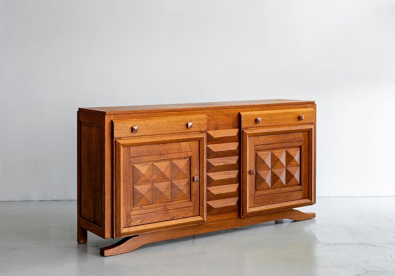 1940s French oak cabinet designed by Charles Dudouyt with 2 drawers and 2 open panels on floating curved legs.