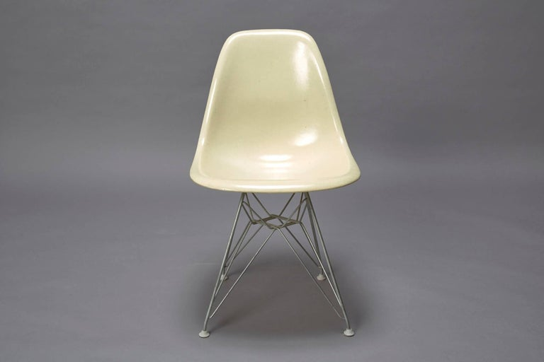 This chair is designed by Charles Eames and produced by Herman Miller in the 1950s. The armless fiberglass bucket/shell chair is on it's original Eiffel base.