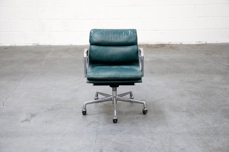 A collectible and sought after leather 'Soft Pad' management desk chair from the Aluminum Group line, designed by Charles and Ray Eames for Herman Miller. Featuring its original vintage green color leather upholstery over five-star aluminum base and