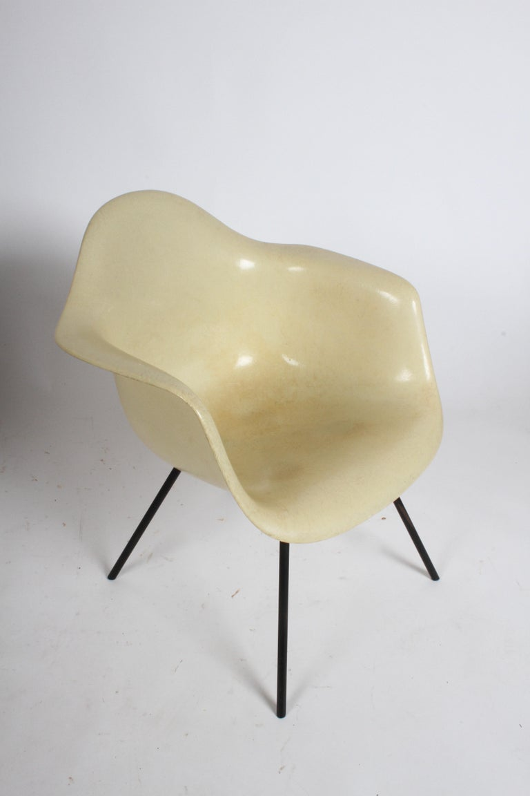 Charles and Ray Eames second generation Zenith shell armchair, black enameled metal legs in X-pattern, large shock mounts, pale yellow fiberglass shell, fiberglass is free of chips, some age related wear to the shell but overall a good example of an
