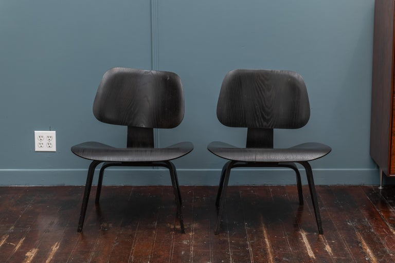 Rare pair of early production (5 x 2 x 5 screw mounts) Charles Eames design LCW (lounge chair wood). Original analine black finish in very good original condition. One rear shock mount is separated but stable and does not affect the form or