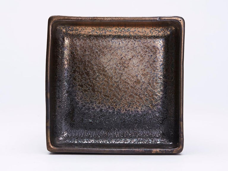 A stylish French Greber art pottery high fired lustre stoneware dish of shallow square form standing on an unglazed foot with oxidised metallic glazes. Made in Beauvais and probably by Charles Greber (1853-1935) the dish is impressed GREBER BEAUVAIS