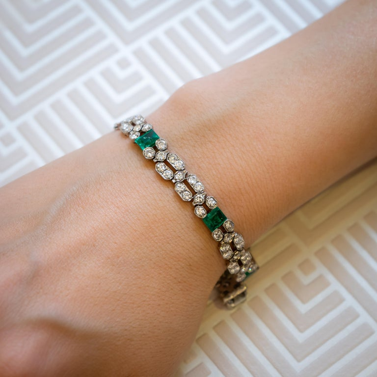 A fine, late Art Deco, French, emerald and diamond bracelet, by Charles Holl, set with six, invisibly set, rectangular, step-cut emeralds, with round brilliant-cut diamonds, set in articulating, millegrain edged, open work panels, mounted in