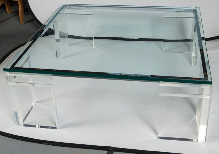 A monumental Charles Hollis Jones Lucite, chrome, and glass coffee table. The glass sits atop four very thick Lucite legs which are connected by 4 pieces of mitered chrome hardware. The top is thick glass with a flat polished edge and sits above the