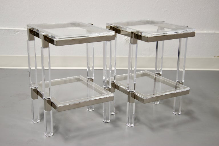 A great pair of Charles Hollis Jones nickel and lucite end tables. These tables are recent production. 14 by 14 inches in dimension and 19 inches tall.