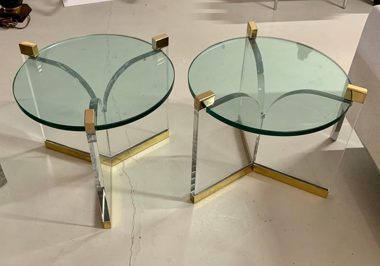 A pair of Charles Hollis Jones trefoil tables in brass, Lucite and glass. These are vintage tables, not new production. The glass top diameter alone is 20 inches and measuring taking into account the ends it is 22 1/2 inches in diameter. The brass