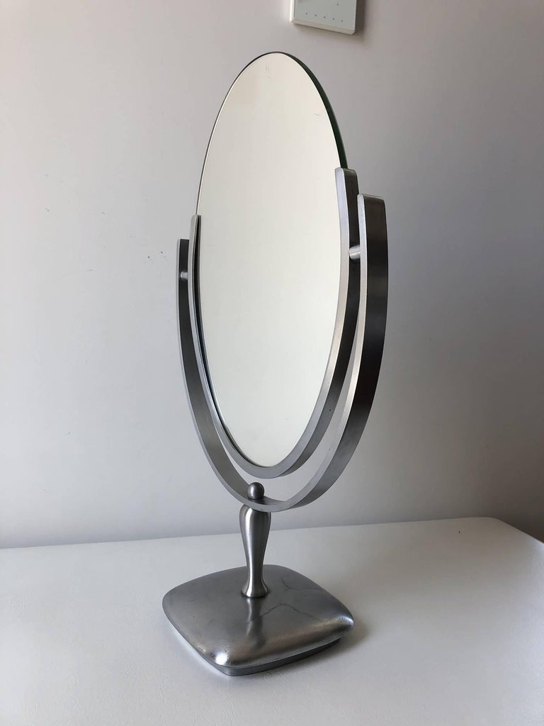 Beautiful oval mirror designed and manufactured by Charles Hollis Jones in the 1960s. The mirror has a satin metal frame and base, the mirror has a beveled finished and is in excellent condition.
