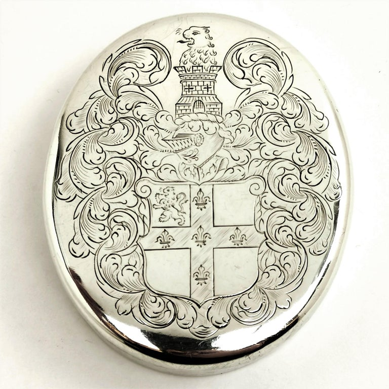 A beautiful classic Charles II Silver oval shaped Tobacco Box with a large engraving on the lid. The cover is engraved with the arms of Hitchcock of Preshute, Wiltshire, crest of another. The base of the Box is plain silver.  Made in London in 1762,