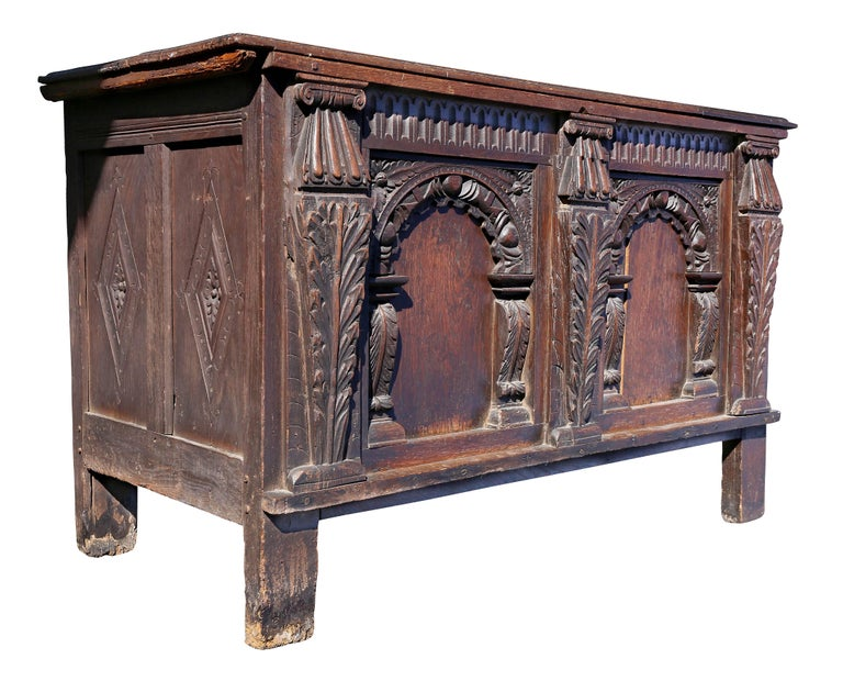 With a two board top over a case section with two panels each with carved arches flanked by acanthus leaf carved columns raised on stile feet.