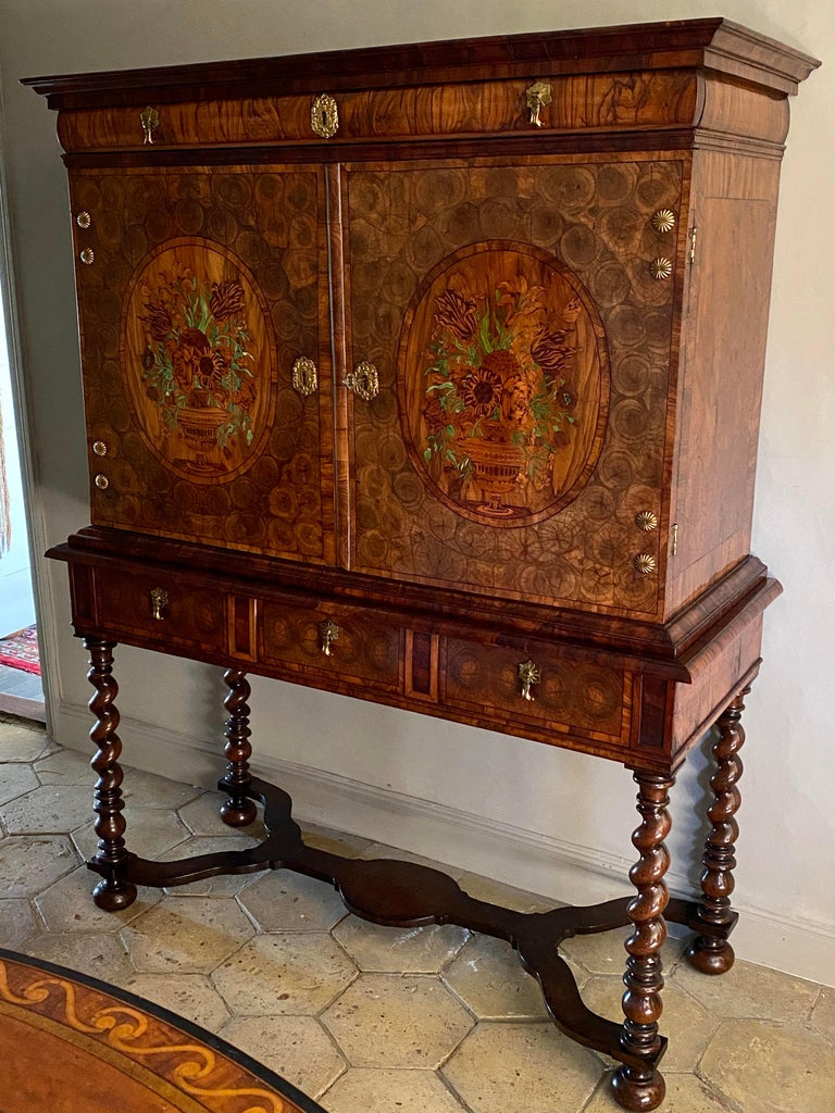 A rare Charles II period (1630-1685) oyster olivewood and walnut marquetry cabinet on stand, of good rich color. Superbly inlaid with oyster veneers, the doors centred with impressive ovals of floral marquetry issuing from urns. These oval panels