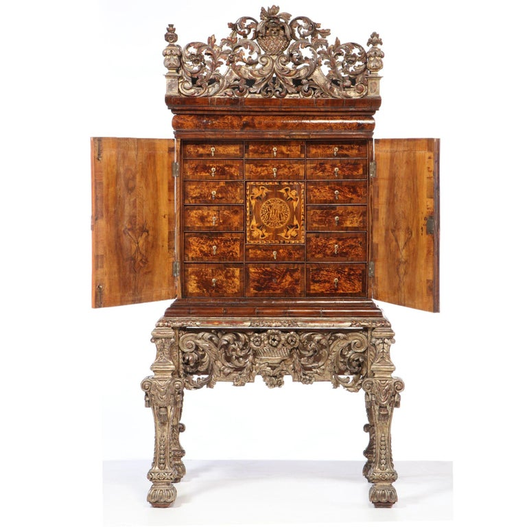 Charles II walnut and mulberry marquetry cabinet on giltwood stand, c. 1650-1670. Giltwood cresting and stand appear to be from a few decades later.    The form of furniture now described as a cabinet developed across Spain and France in the 16th