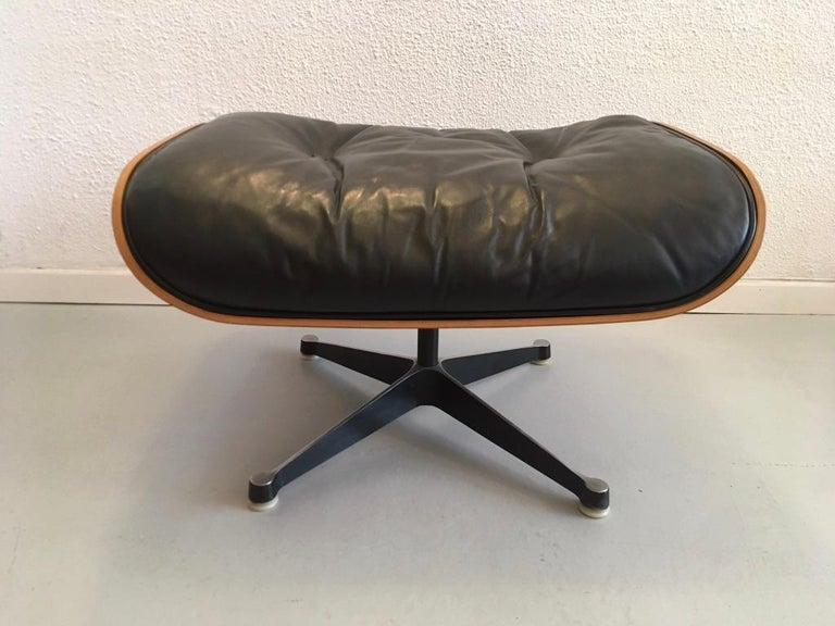 Charles & Ray Eames black leather and rosewood ottoman for lounge chair, Herman Miller, circa 1970s Manufacturer label underneath. Black base with white glides. Cushion filled with feathers. Original vintage very nice condition.