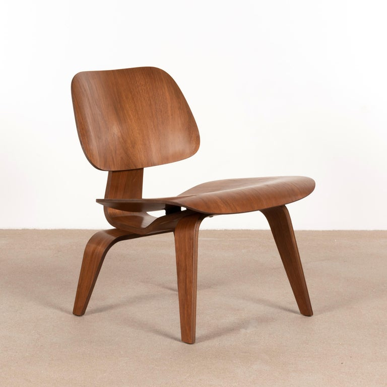 Iconic LCW lounge chair in walnut plywood. The veneer and chair is in very good condition with nice patina and wood grain. Early Herman Miller edition after they took over the production from molded plywood division.