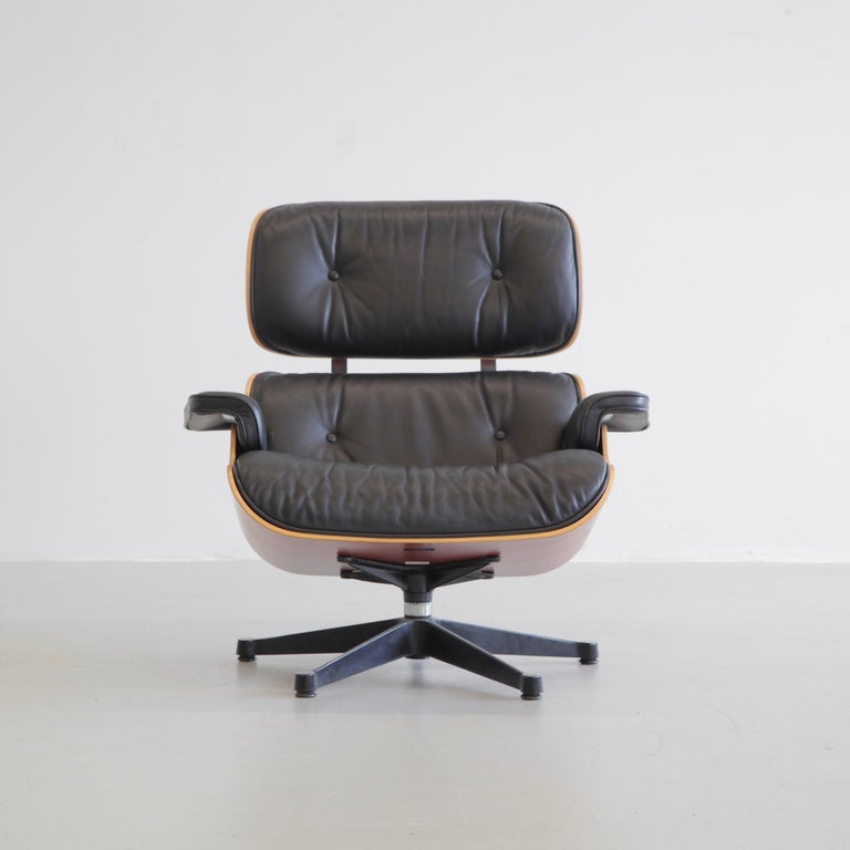 Lounge chair and ottoman, designed by Charles and Ray Eames in 1956. Germany, Vitra, 1999.  Beautiful original lounge chair with cherrywood shell and subtle black leather upholstery. The original maker's labels are both present under the chair and