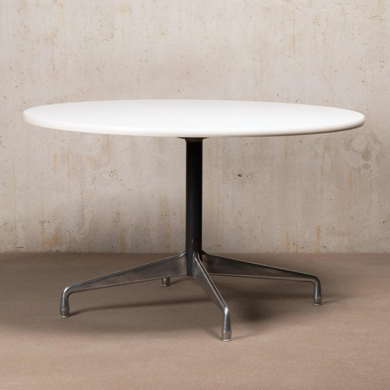 Early dining table by Charles and Ray Eames for Herman Miller. Chrome plated cast aluminum base with (height) adjustable glides and white laminated table top with rubber edge. The tabletop has a diameter of 122 cm (47 3/4 inch), suitable for 4