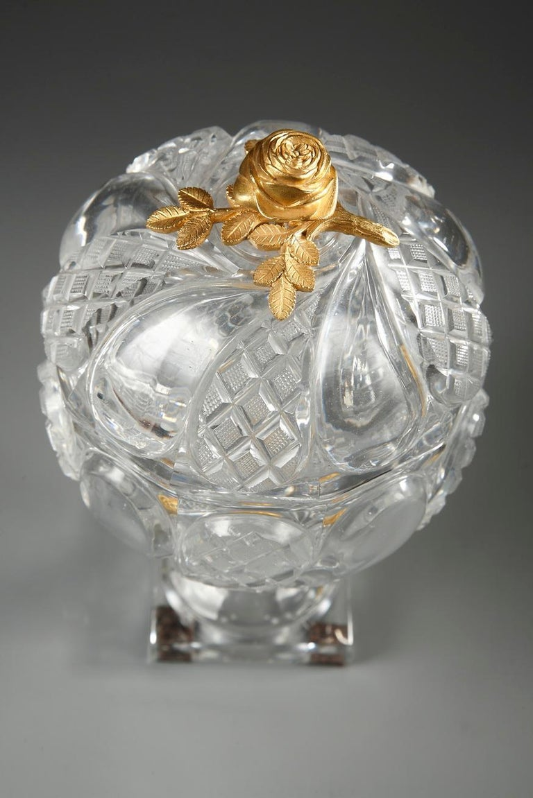 A cup in Baccarat cut-crystal with fine twisted patterns alternating with twisted diamond-shaped patterns in high relief. The lid is topped by a gilt bronze rose. Foot adorned with an ormolu ring, chiselled with flowers, resting on a small square