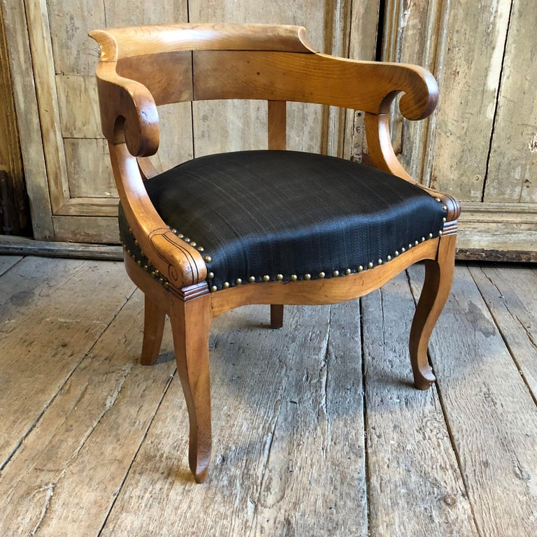 "A Charles X period ""Fauteuil de bureau"" with a yoke-back, low arms and upholstered seat on cabriole legs, in blonde fruitwood, circa 1820.  The Charles X style, also known as ""Restauration Period Style"" and it's use of ""bois Claire"" or light woods,"