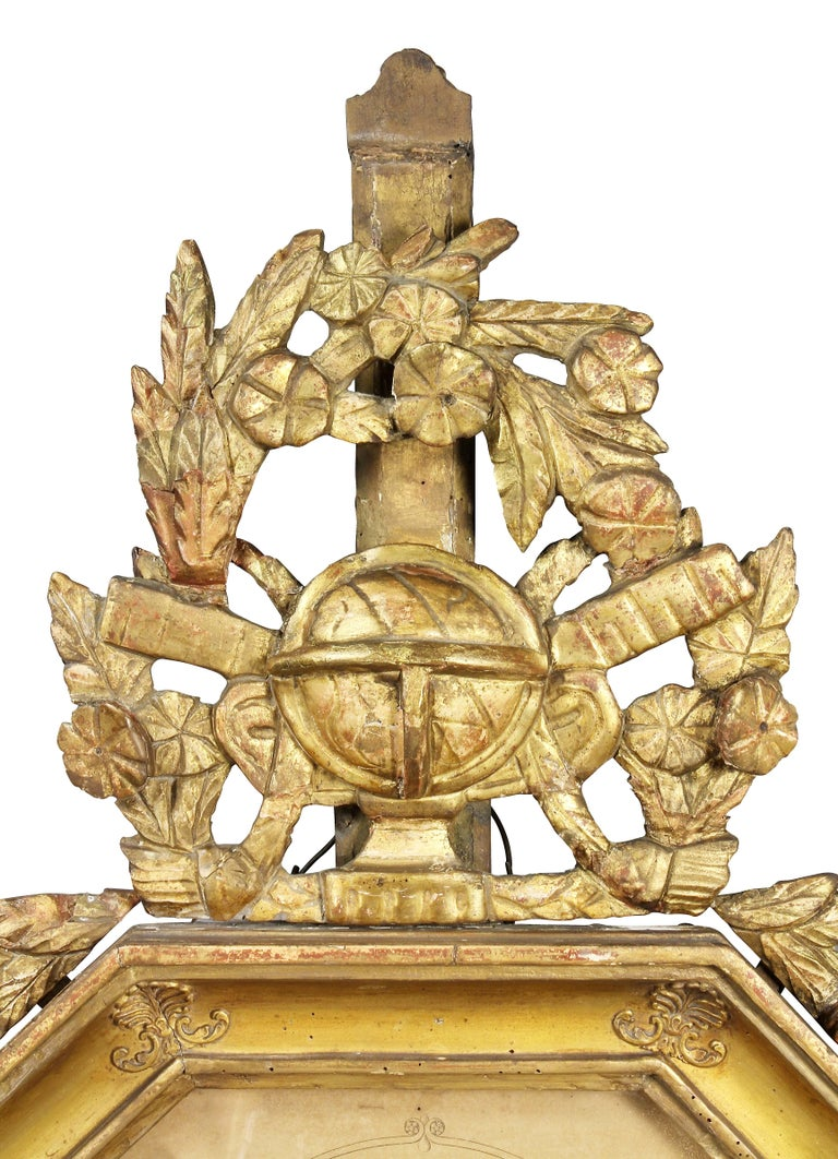 With leaf and floral crest with central orb over an octagonal glass and a paper dial set in a conforming frame.