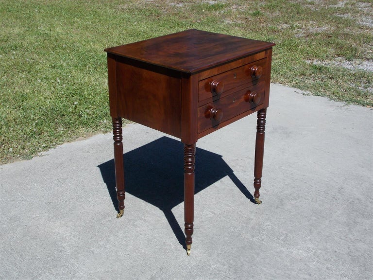 Charleston Federal mahogany two-drawer stand with a carved molded edge top, original wood knobs, and resting on turned bulbous ringed legs with the original brass cupped casters. Early 19th century. Secondary wood consist of poplar.