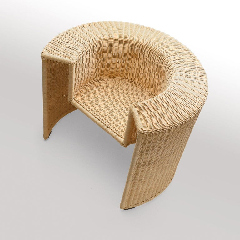 An example of skillful craftsmanship in a sophisticated, modern design, this armchair by Mario Botta comprises a structure in white-painted metal covered entirely by natural wicker. Woven by hand, the gray and beige streaks that may appear on the