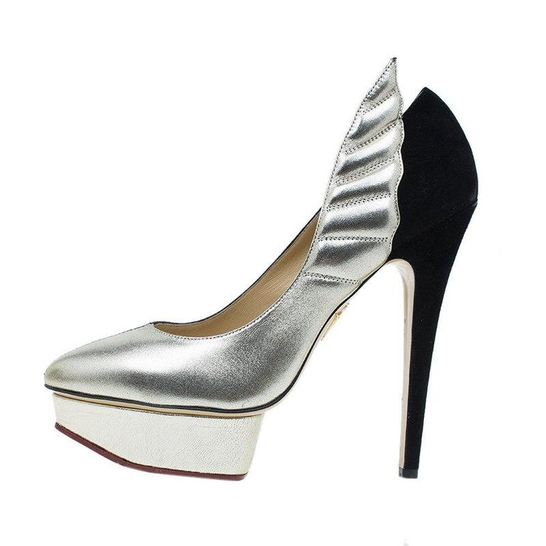 Fuse exotic with glamorous by flaunting this pair of Charlotte Olympia heels. Crafted with part black and part silver leather, they feature pointed toes over bold platforms. They are lined with beige leather and are accented with 15 cm heels. With
