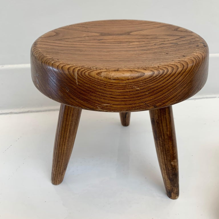 Collectible oak stool by Charlotte Perriand in France, Circa 1953. Two available. Priced individually. Very good condition with slight wear and excellent patina.