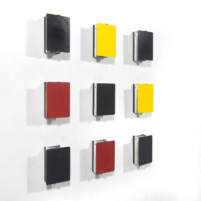 This spectacular set of Perriand wall sconces is exceptional not only for the number of lamps, but the inclusion of lamps in uncommon red, yellow, and particularly gray. A brilliant minimal design by Perriand, the pivoting shades shield glare and