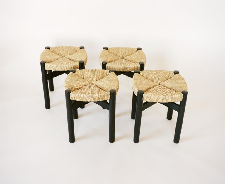 A set of four black oakwood stools with woven rush seats by Charlotte Perriand, circa 1950. Perriand produced these stools after her 6 year stay in Japan. Returning to Paris, Perriand was commissioned to design the interiors of Hôtel le Doron in