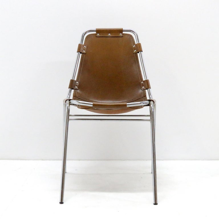 Iconic leather and metal side chairs selected by Charlotte Perriand for the Ski resort Les Arcs in 1960, with chrome tubular frame in great condition and high quality thick leather seat with a fantastic patina to the leather.
