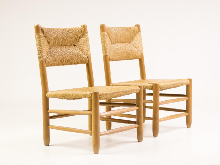 Pair of chairs designed by Charlotte Perriand, circa 1950. Manufactured in France. Seemingly simple but very refined design. The rear legs elegantly bent to form the backrest supports. A recess in the backrest supports enables the rush surface to