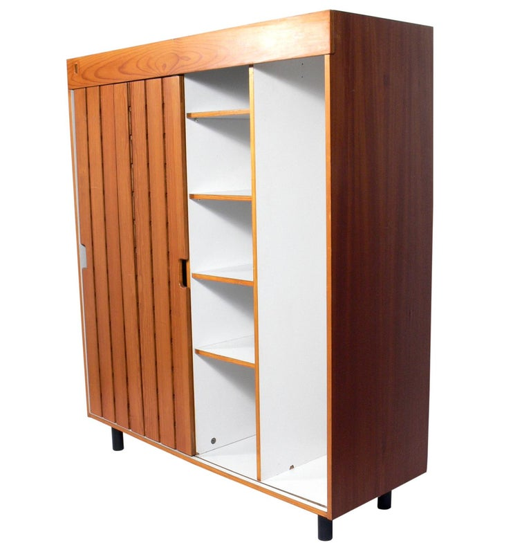 Charlotte Perriand wardrobe from Les Arc Ski Lodge, France, circa 1960s. It offers a voluminous amount of storage with the single door sliding to reveal two large compartments on the left and  two large compartments on the right, one with shelves,