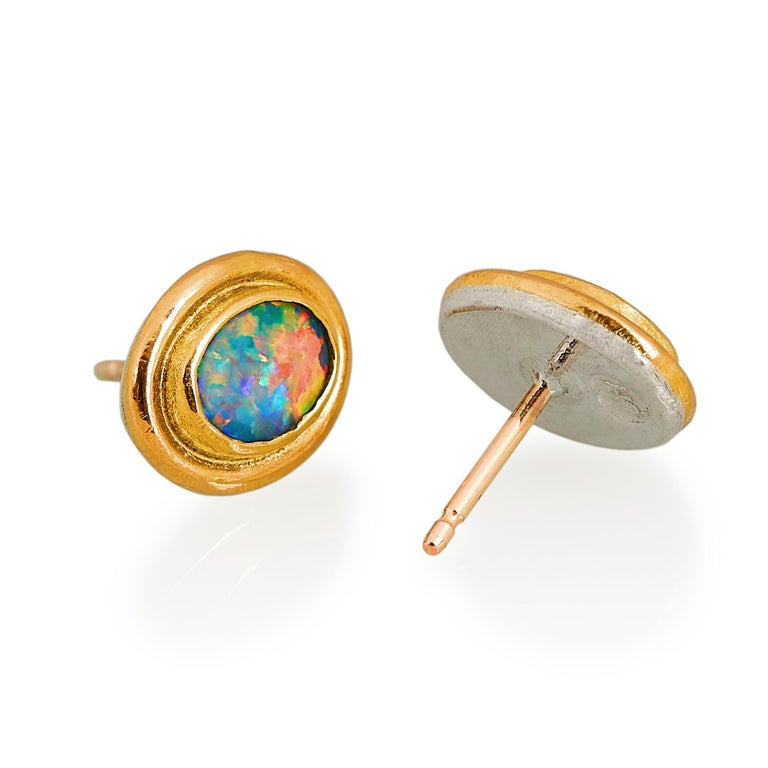 Handmade Charmian Harris stud earrings that can easily worn on any occasion. They are made with bright doublet opals that refract almost all the colours of the rainbow. The opals are set in ample 22 karat gold which is backed on silver and they have