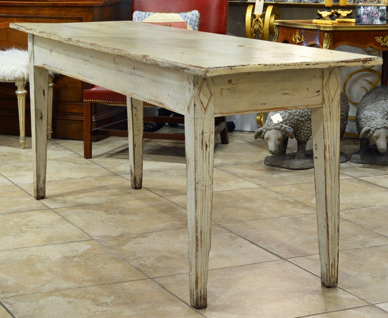This 19th century Gustavian style farm table has a fetching look with a beautifully worn paint layer and fluted tapering legs surmounted by carved diamond reliefs. Sometimes less is more, and the charming simplicity of this table will compliment any