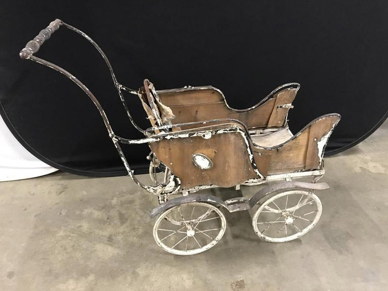 Antique baby carriage constructed of metal and wood, the buggy makes a wonderful doll stroller, use in a garden for plant display, plant stand or garden decoration.