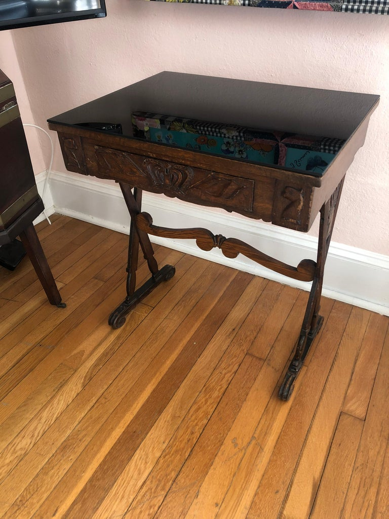 A masculine wonderfully weathered carved oak end table having single drawer with crown decoration and two animal motife heads that look like chess pieces on either side, as well as handsome X motife legs also decorated with crowns. Top has a
