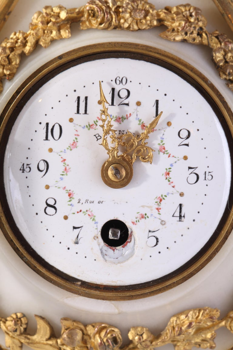 Charming small round Cartel clock in white marble and gilt bronze flowers, hung by a ribbon bow. The enameled dial with painted flowers garlands is signed Bernoux, and circled by sparkles.