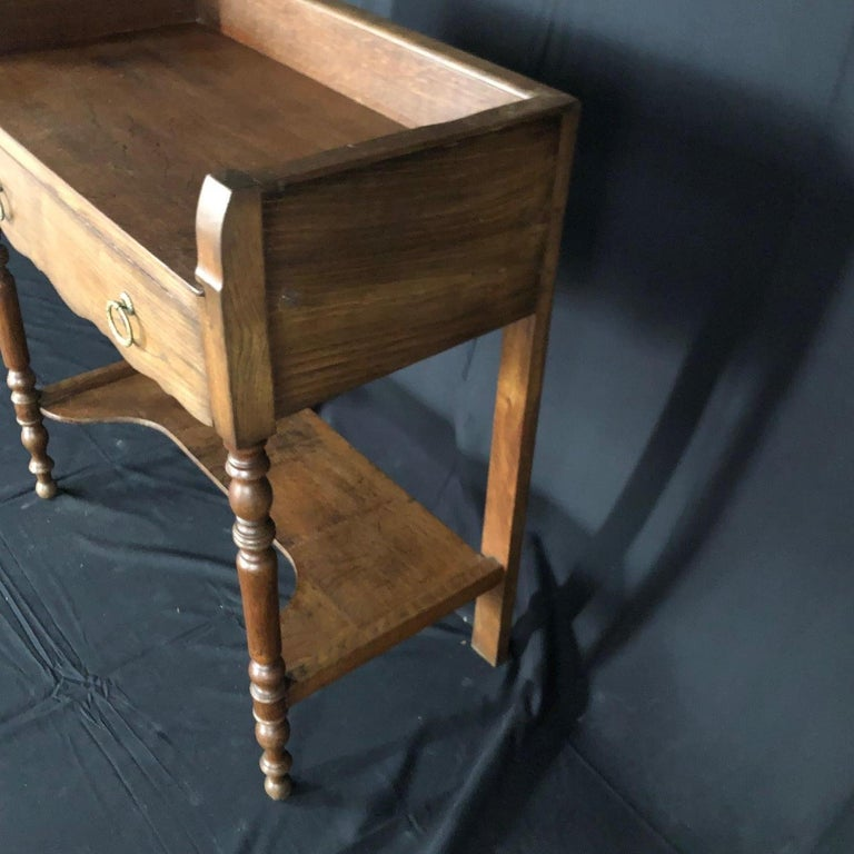 A French oak washstand having full length drawer with bronze pulls and beautifully turned front legs. The lower shelf has a shaped front. Hanging rod on the left side. Functional and beautiful! #5132