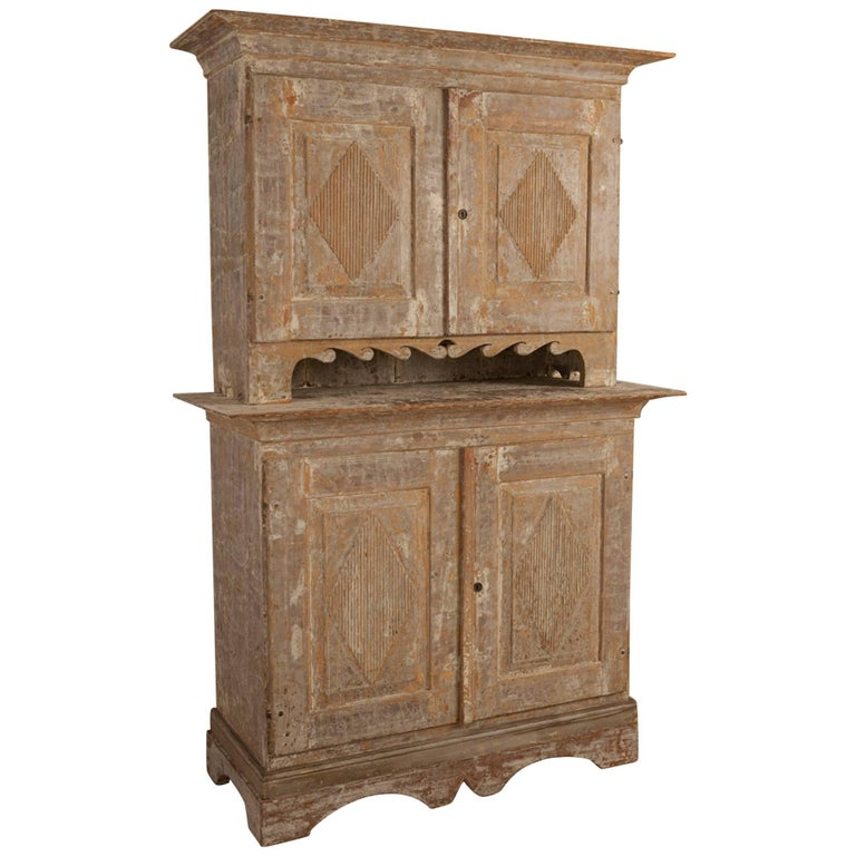 Charming Gustavian cabinet, circa 1790, origin Sweden, upper cabinet with scalloped wave pattern and hand-carved diamond patterns on each door sits atop the lower cabinet.   The beautifully layered, hand-painted original color and elegant surface