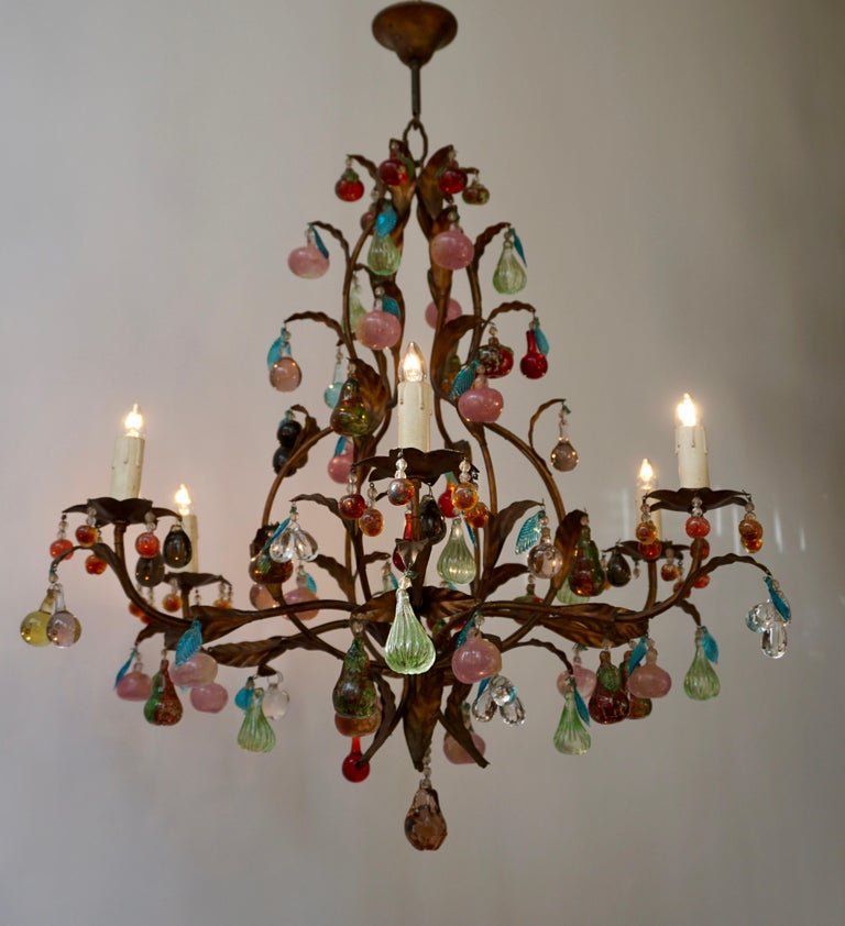 Charming Italian brass and Murano glass chandelier embellished with fruit pendants and drops in colored glass. The different fruits, like grapes, pears and apples, in solid Murano glass are and also the molded leaves present sumptuous colors.
