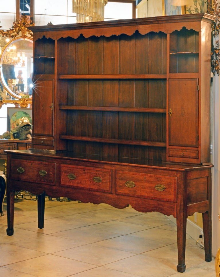 This welsh dresser consists of two parts. The upper part features a moulded corniche and a scalloped frieze above three plate rack shelves flanked by cupboards and small drawers with mahogany banded fronts above which smaller open compartments with