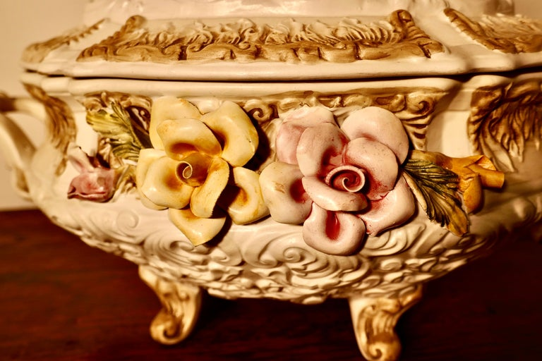 Charming late 20th century Capodimonte tureen with lid  A delightful piece all fully marked beneath, the lid has 2 children on the top and the bowl has handles and the trademark bocage and flowers on the front Not new but as far as we can see no