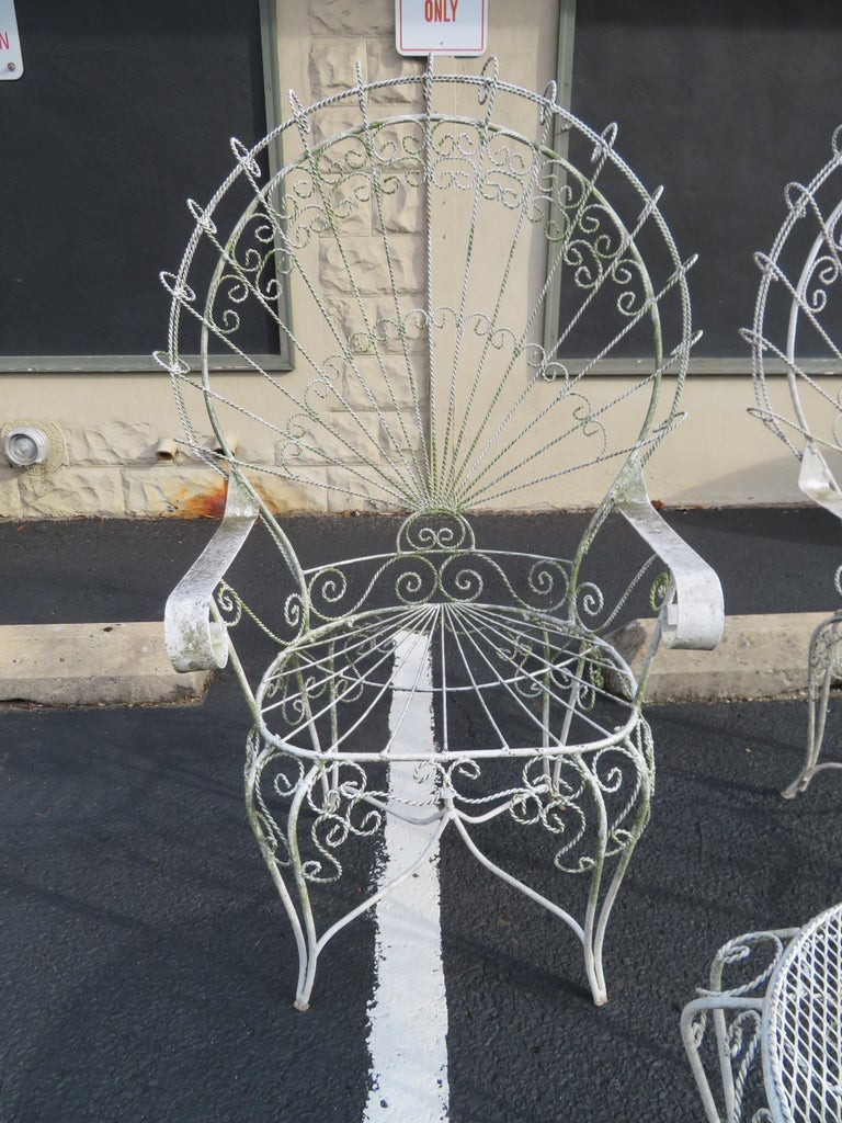Gorgeous pair of Salterini ornate wrought iron twisted wire fan back patio chairs with matching side table. This pair will have a new coat of white paint before they are shipped. There are no cracks or breaks to the frames-sturdy.