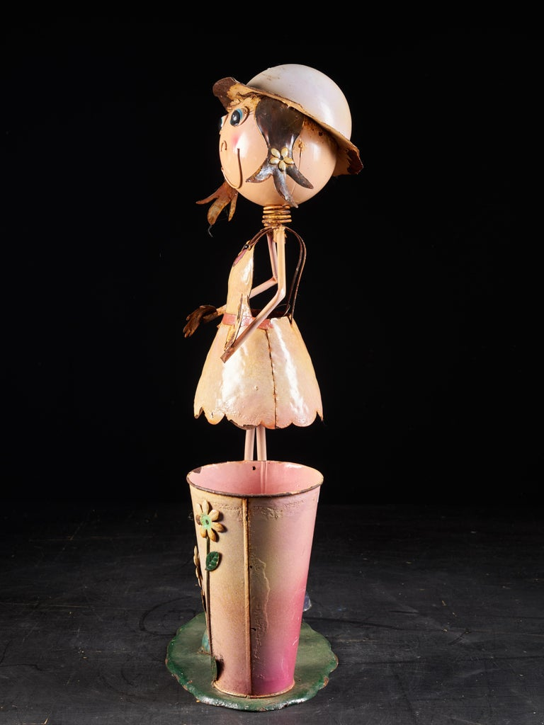 This lovely model of a cartoon woman is made out of tin and probably from the USA. She stands on a green base and next to her there is a blush and light pink colored tin flowerpot. The pot is decorated with three flowers in relief in green and