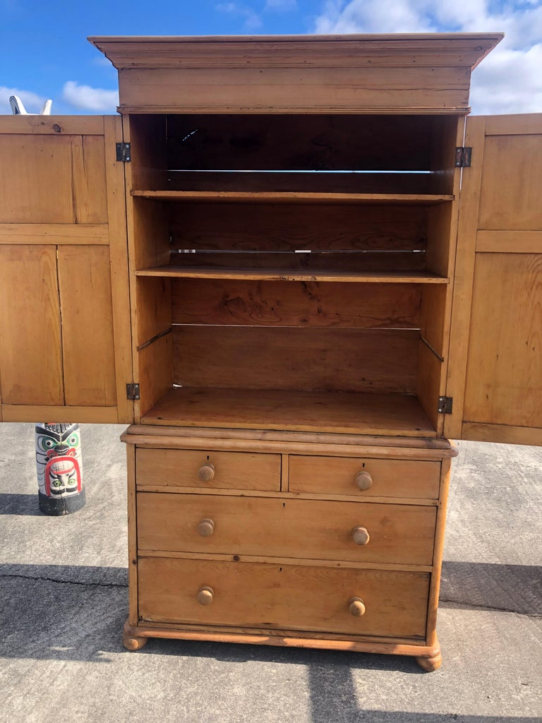 A rustic antique natural pine cabinet wardrobe in two pieces; top has panel doors that open to roomy storage, once used to house a television. There are two shelves currently. Bottom has 4 dovetailed drawers, 2 large with 2 smaller on top. The