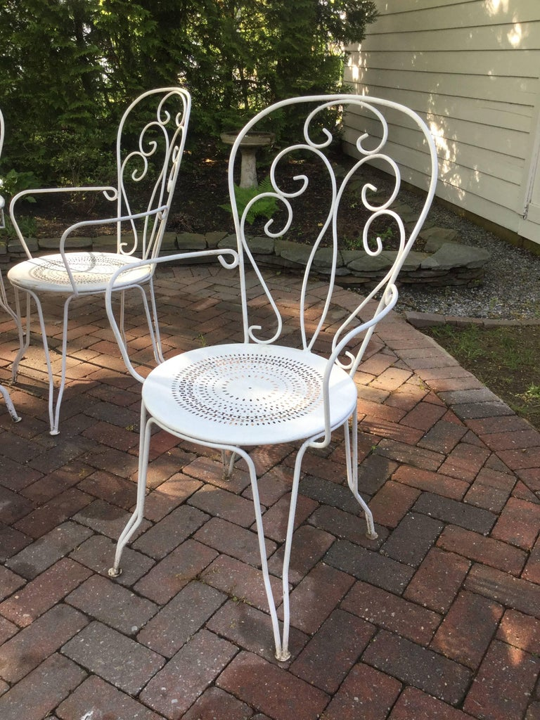 Classic vintage French cafe set having a round iron table and set of 6 matching chairs. Chairs are 39