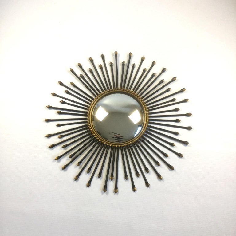 Large sunburst mirror or (witch mirror) manufactured by Chaty Vallauris based in Provence in France. Metal and gild painted frame with original convex mirror.