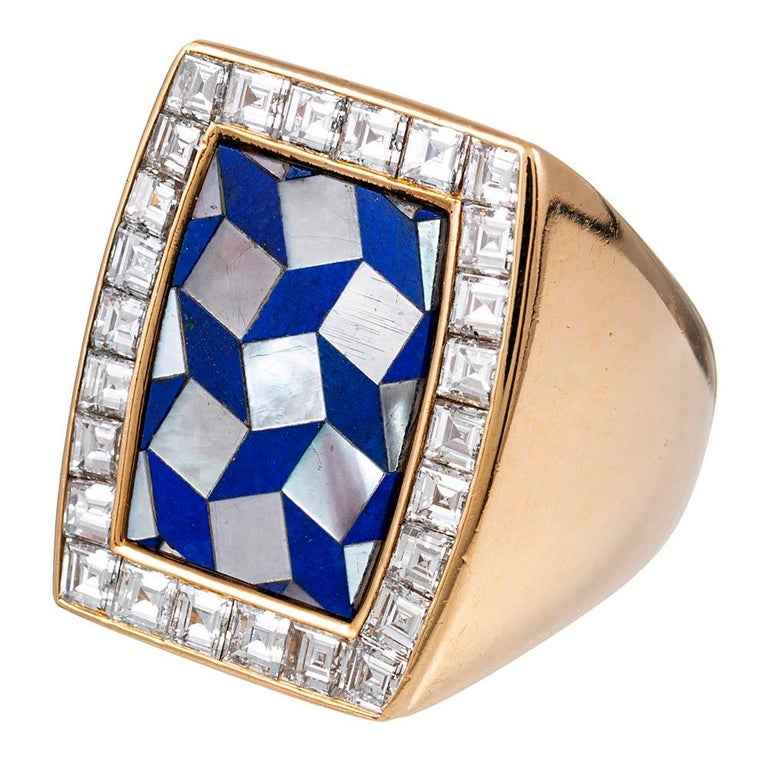 This bold ring is suitable for a lady or a gentleman. The top is an intricate mosaic of lapis and mother of pearl, with a single frame of square cut white diamonds. The diamonds weigh approximately 4 carats in total. The ring is made of 18 karat