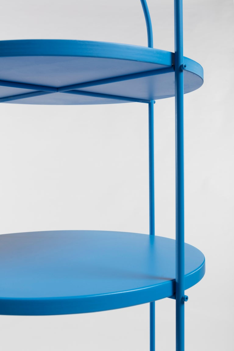 Tables on one or more levels, furnish ironically without remaining unnoticed. Ideal companions for public and private environments and contexts. The structure is a curved metal round, with bolted beams, shelves and container in matte lacquered